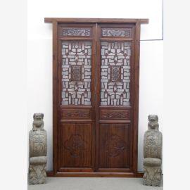 La porte chinoise en bois dur foncé avec des détails élaborés.